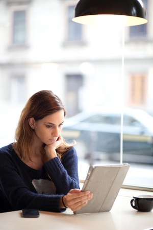 Authentic image of a young woman using tablet computer in a cafe Stock Photo - 17537461