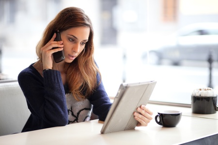 Candid image of a young woman talking on the phone in a cafe  Selective focus  photo
