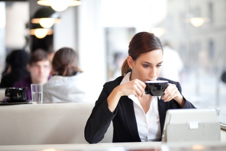 Businesswoman having a cup of coffee while reading an article on her tablet computer  In a coffee shop  photo