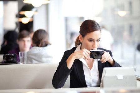cafe internet: Empresaria con una taza de café mientras lee un artículo sobre su Tablet PC en una cafetería
