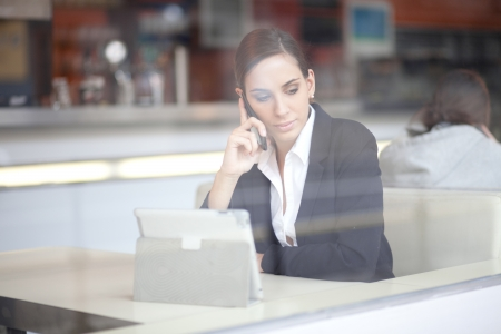 business woman phone: Businesswoman talking on the phone in a coffee shop
