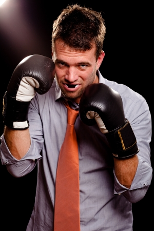 Businessman with boxing gloves guarding his face  High contrast  photo