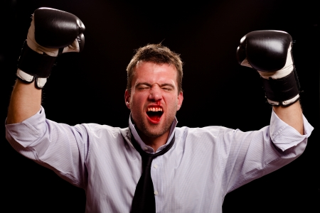 Victorious boxing businessman wth blood pouring out of his nose and mouth photo