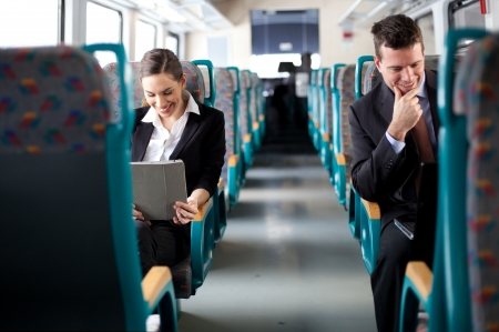 commuting: Business on the move  Business people using computers on the train  Selective focus
