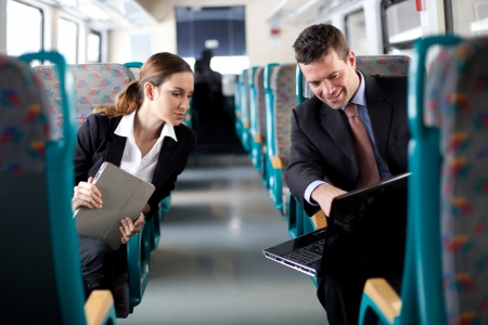 Business people comparing notes on the train Stock Photo