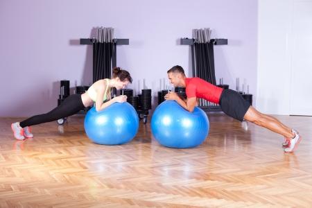 Core  balance training. Couple doing plank exercise using exercise balls photo