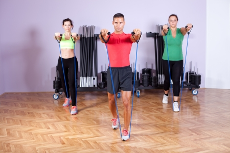 resistance: Small group of people doing shoulder exercses using resistance bands