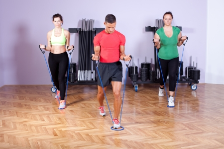 rubber band: Small group of people doing bicep exercise using resistance bands