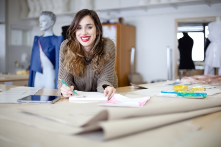Happy fashion designer working on her designs in the studio Stock Photo - 17702822