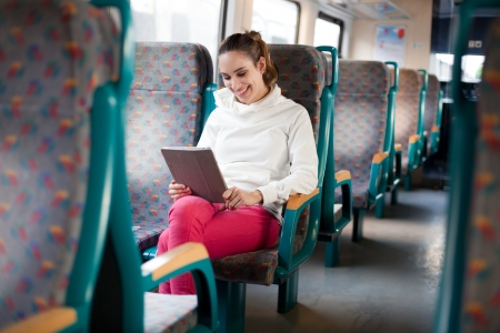 student travel: Cheerful young woman using tablet computer on the train