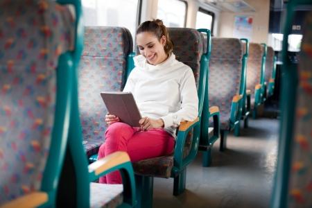 passenger buses: Mujer alegre joven con tablet PC en el tren