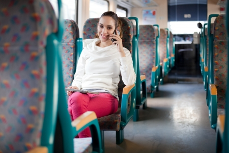 Young woman talking on the phone on the train photo