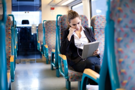subway train: Businesswoman listening to music and using tablet computer on the train