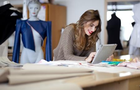 estilista: El dise�ador de moda que usa el ordenador tableta en el estudio Foto de archivo