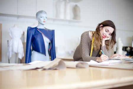 fashion clothing: Fashion designer working on her designs in the studio Stock Photo