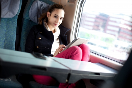 public transportation: Young woman using tablet computer on the train