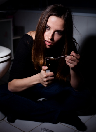 Young woman heating up heroin before injecting photo