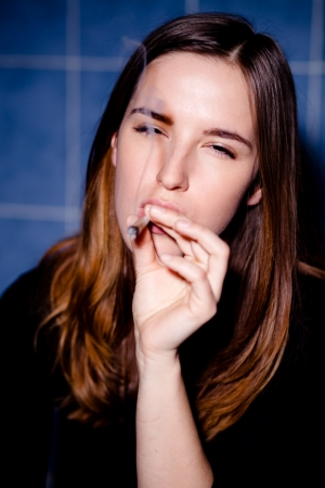 drug use: Getting high. Young woman smoking a joint. Selective focus.