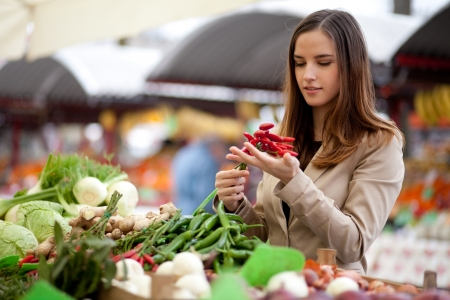 Young woman buying red hot chilli peppers at the market photo