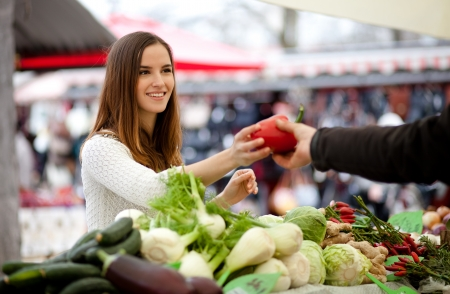 Farmer passing young woman a red pepper at the market Stock Photo