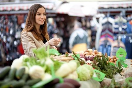 campesino: Mujer joven apuntando a los productos que quiere comprar en el mercado de los agricultores Foto de archivo
