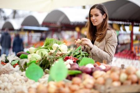 joven agricultor: Joven mujer recogiendo productos frescos en el mercado Foto de archivo