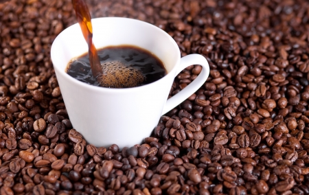 steaming coffee: Coffee being poured in a cup  Decorated with coffee beans