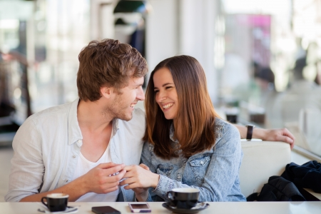 Candid image of young couple smiling in a coffee shop. Shallow DOF, focus on mans eyelash.