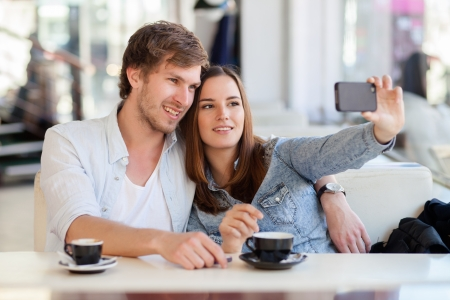 Young woman taking a photo with her mobile phone in a cafe. Shallow DOF, focus on young man's eye. Stock Photo - 19125595