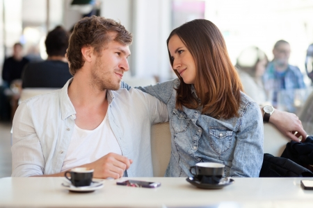 couple talking: Young couple in lover staring at each other. In a coffee shop. Stock Photo
