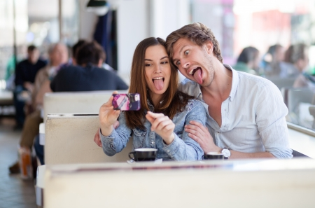 Young couple taking photos of themselves, making crazy faces. In a cafe.