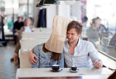 mujer fea: Hombre joven que abraza a su novia con una bolsa de papel sobre su cabeza. En una cena.
