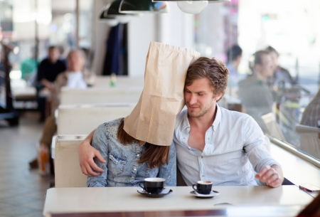 Young man hugging his girlfriend with a paper bag over her head. In a diner. Stock Photo