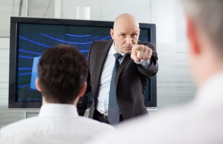 executive courses: Angry boss pointing his finger at his employee during a meeting  Sghowing who