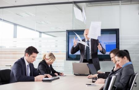 jefe enojado: Mad CEO tirando documentos en una reuni�n subordinados mirando hacia abajo, con miedo de hacer contacto visual Foto de archivo