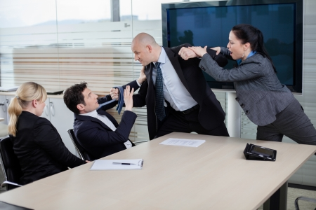 aggressive people: Businessman attacking his colleague at a meeting, grabbing him by the tie and getting ready to punch him in the face  Emotions running high