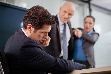 Businessman punching his colleague in the face at a meeting  Businesswoman is trying to stop the fight  Stock Photo - 19203356