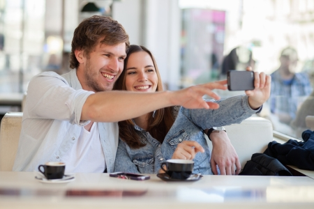 dating: Young couple taking a photo of themselves in a cafe