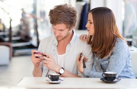 novios enojados: Mujer joven frustrada pidiendo su novio a dejar de jugar con su teléfono Foto de archivo