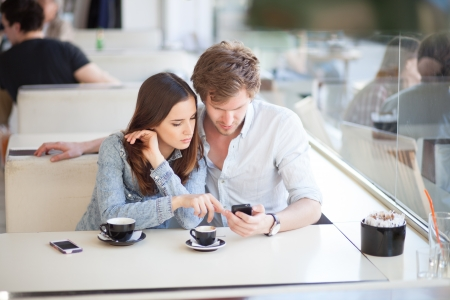 coffee shop: Young couple surfing the web   looking at photos on mobile phone  In a cafe  Stock Photo