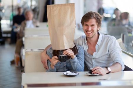 mujer fea: Pareja joven tomando un caf� en un caf�. Mujer joven, que llevaba una bolsa de papel sobre su cabeza est� mezclando az�car en el caf�.