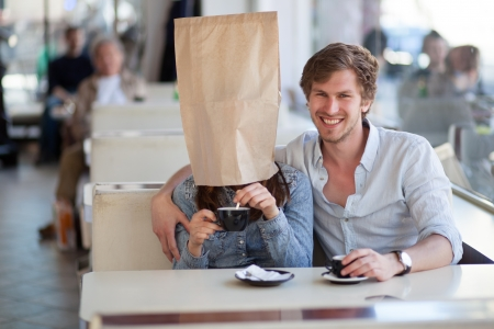 ugly girl: Young couple having coffee in a cafe. Young woman, wearing a paper bag over her head is mixing sugar in coffee.