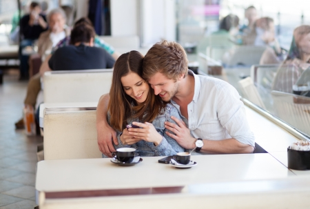 Young couple in love surfing the web  looking at photos on mobile phone. In a cafe. photo