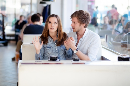 girl fighting: Young couple arguing in a cafe. Shes had enough, boyfriend is apologizing. Relationship problems.