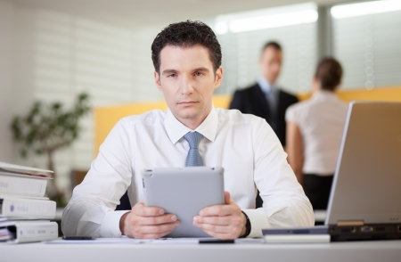 Overworked tired businessman sitting at his desk in the office  Looking at camera  Stock Photo - 19380093