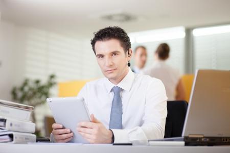 Confident businessman sitting behind the desk photo