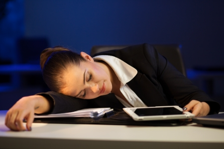 Tired businesswoman falling asleep in the office late at night photo