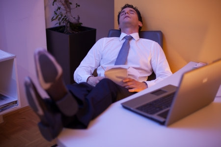 Tired businessman falling asleep while eating chinese food late at night in the office photo