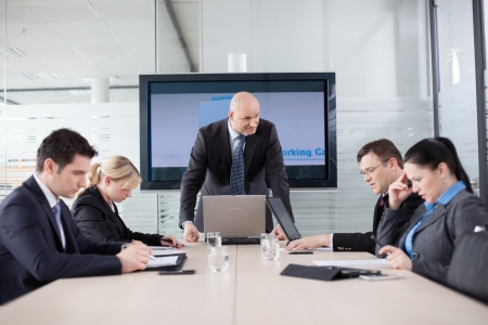 Angry boss at the meeting. Employess are looking down, afraid to make eye contact. Stock Photo