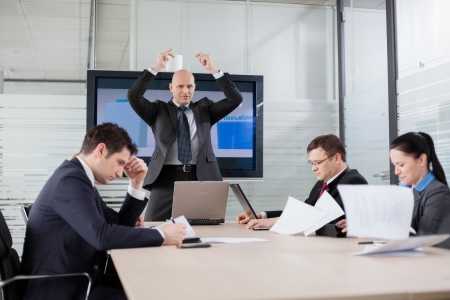 aggressive people: Angry and disappointed boss throwing documents during briefing